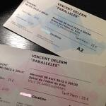 Photos de deux billets pour le concert de Vincent Delerm à Sarreguemines le 8 avril 2015 posés sur une table noire