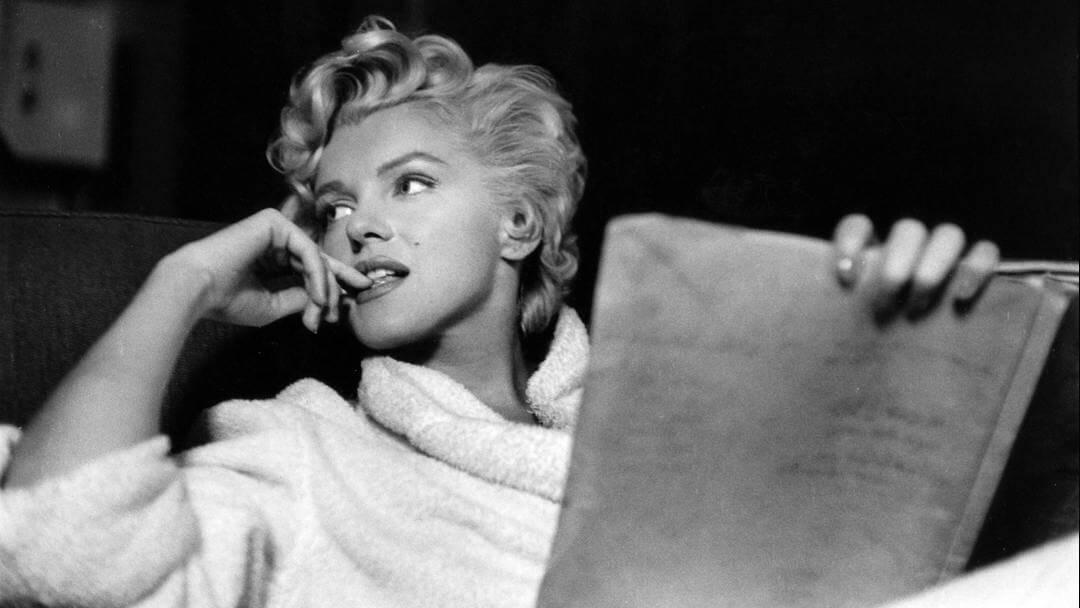Photo de Marilyn Monroe en peignoir de bain, lisant allongée la main droite tenant sa tête
