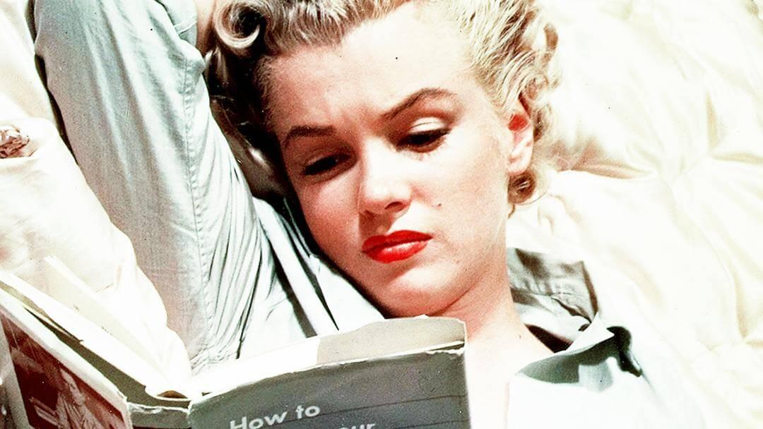 Photo de Marilyn Monroe liasant allongée le bras droit replié derrière la tête