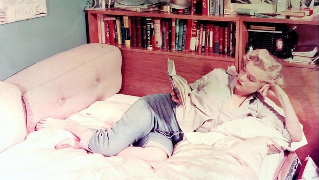 Photo de Marilyn Monroe lisant sur un canapé-lit se tenant la tête avec le bras gauche
