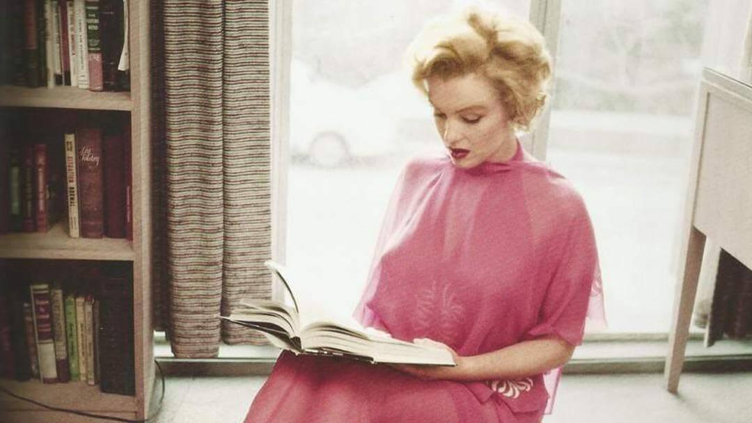 Photo de Marilyn Monroe lisant en déhabillé rose
