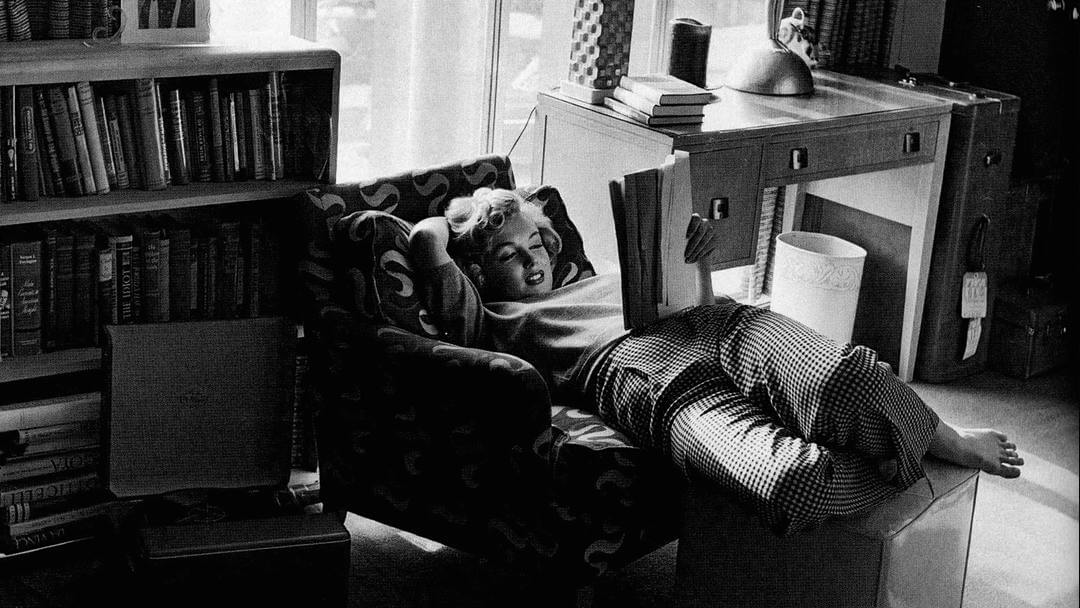 Photo de Marilyn Monroe lisant allongée sur un fauteuil et un pouf