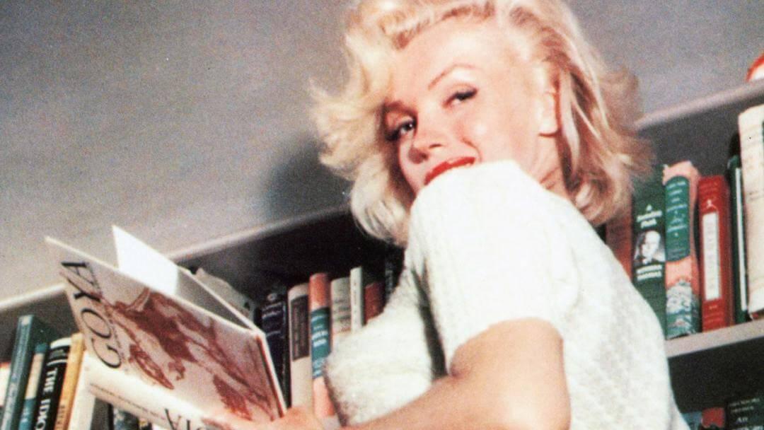Photo de Marilyn Monroe lisant un livre sur Goya en haut d'un escabeau en haut d'une blibliothèque