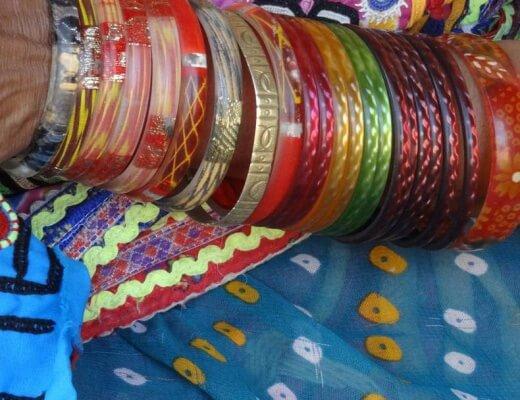 Photo couleur en gros plan d'un avant bras couvert de bracelets bigarrés sur un vêtement bariollé à dominante bleue