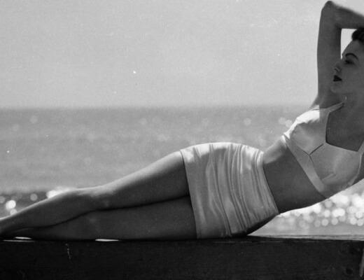 Phot en noir et blanc d'Ava Gardner allongée sur une plage le bras droit derrière la tête
