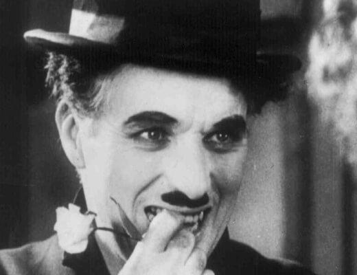 Photo noir et blanc de Charlie Chaplin en Charlot en train de sourire une rose blanche dans la main