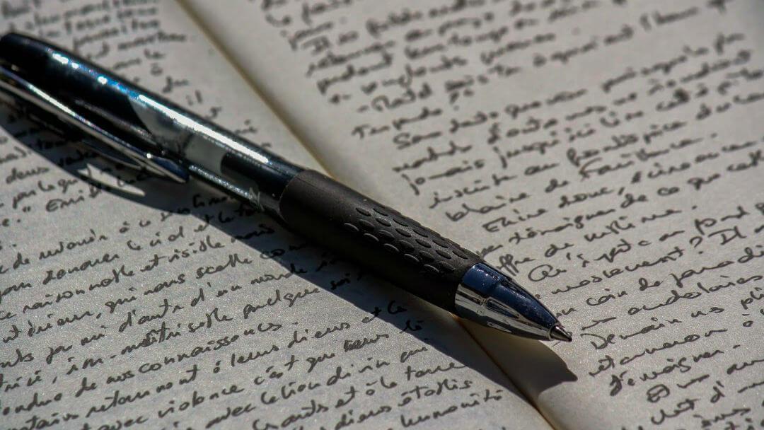 Photo d'un stylo posé en travers d'un carnet d'écriture