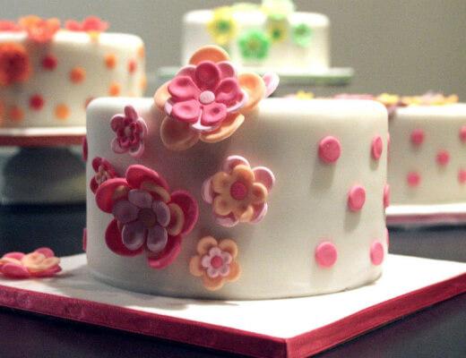 Photo de plusieurs gâteaux à glaçage blanc et motifs floraux de couleur