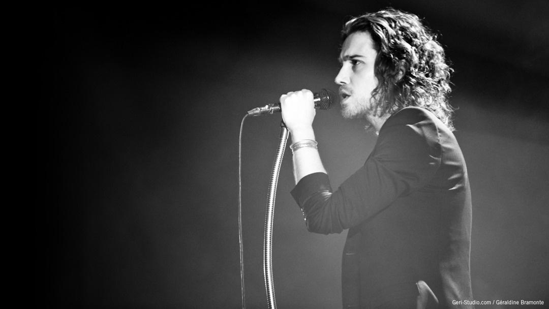 Photo de Julien Doré lors du LØVE Tour, vêtu d'une veste noire la main gauche sur le micro