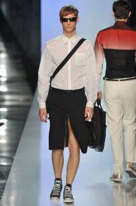 Photo d'un mannequin homme lors d'un défilé portant une jupe JP Gaultier noire fendue devant