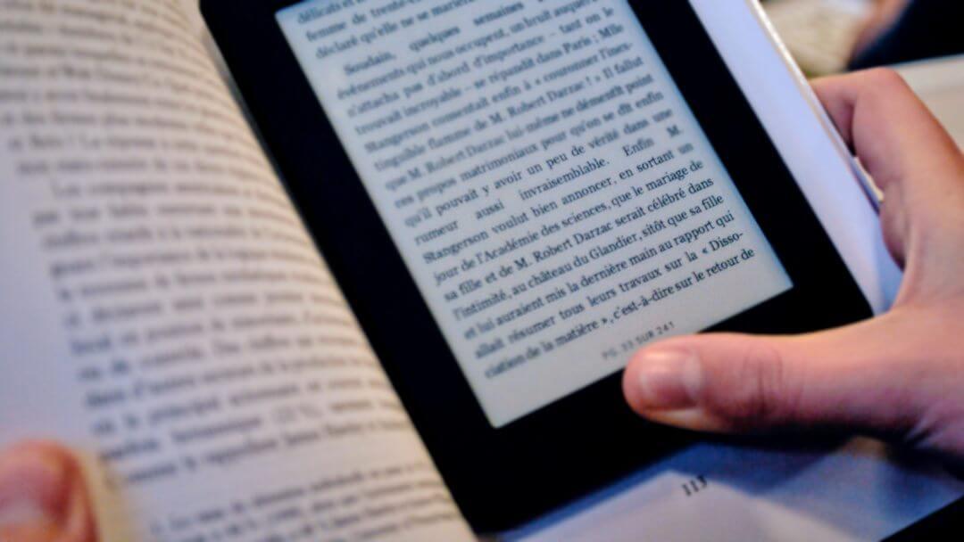 Photo d'une liseuse électronique sur un livre tenu par à mains