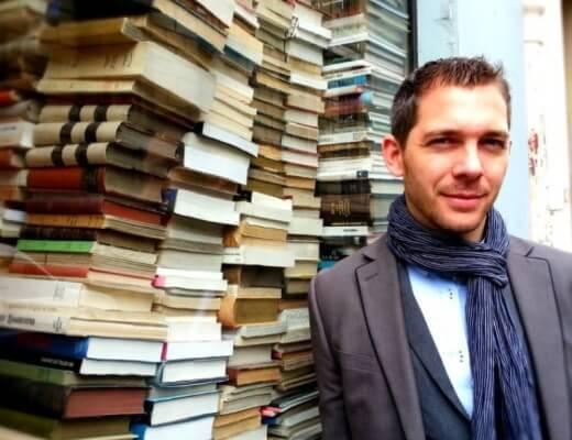 Portrait photo de Romain Puértolas devant un empilement de livres