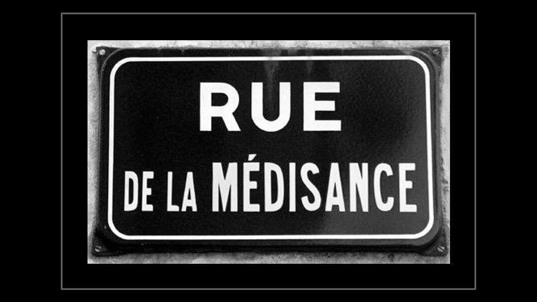 Photo d'une plaque de rue intitluée Rue de la médisance sur fond noir avec un cadre filet gris
