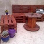 Photo d'un salon de jardin en palettes avec une touret en guise de table