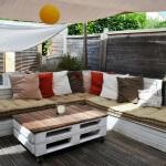 Photo d'un salon de jardin en palettes de récuperation sur une terrasse bois avec velum