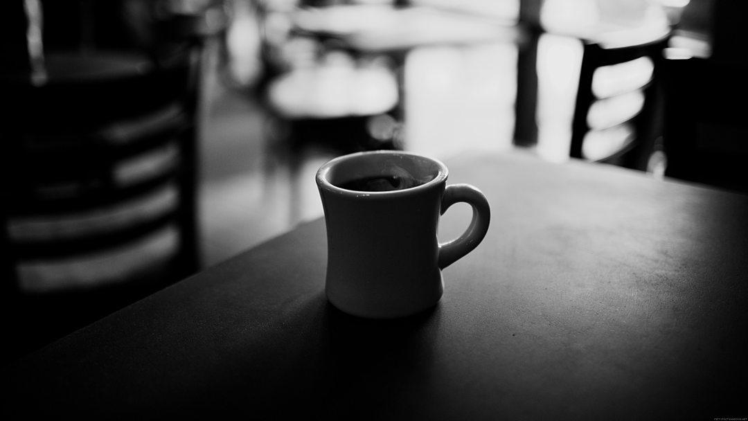 Photo en noir et blanc d'un gros plan d'une tasse de café sans soucoupe posée sur une table de bar avec en arrière-plan flouté des chaises