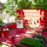 Photo d'une terrasse en palettes peintes en rouge avec du mobilier de récupération assorti