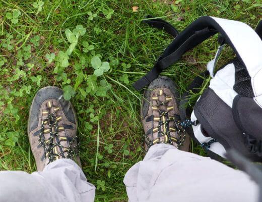 Photo en plongée de chaussures et d'un sac de randonnée sur fond d'herbe